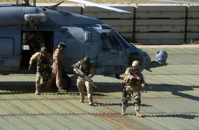 US Navy (USN) SEAL Team Members armed with a 7.62mm M60E3 light machine gun and a 7.62mm M240E machine gun, disembark from a HH-60F Seahawk helicopter at an insertion point during a Non-Combatant Evacuation Operation (NEO) training exercise conducted during DESERT RESCUE XI. The exercise is the premiere Search And Rescue (SAR) training exercise involving all branches of the US Military and is conducted at the ranges at Fallon Naval Air Station (NAS), Nevada (NV)