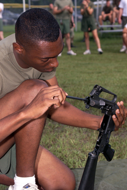 A US Marine Corps (USMC) troop from Marine Wing Headquarters Squadron-2 (MWHS-2) races to quickly put his Colt 5.56mm M16A2 Assault Rifle together during a relay race as part of a field meet held at Marine Corps Air Station (MCAS) Cherry Point, North Carolina