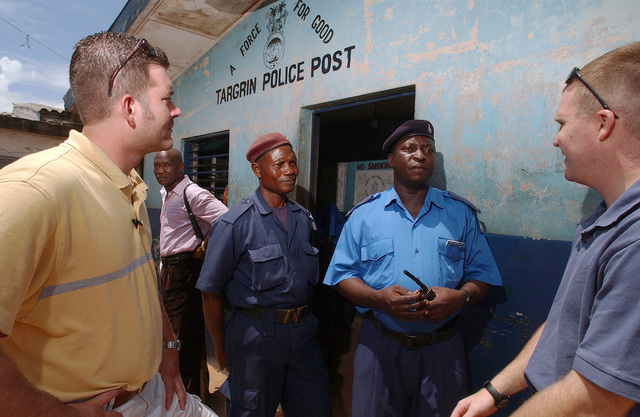 US Air Force (USAF) Special Agents (SA) George Breed (foreground left) and SA Vance Little (right), Air Force Office of Special Investigations (AFOSI), speaks with a local police officers while deployed with the 398th Air Expeditionary Group (AEG), at the Targrin Ferry Terminal located in Targrin, Sierra Leone, during Joint Task Force (JTF) Liberia