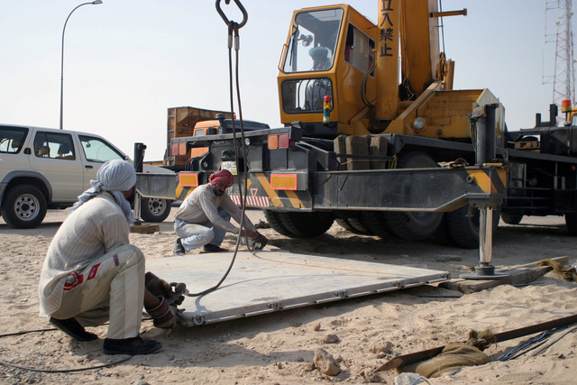 Third Country Nationals (TCN) attach cables to a 463L pallet before a crane moves it at Ahmed Al Jaber Air Base (AB), Kuwait during Operation ENDURING FREEDOM