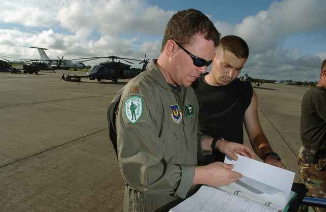 US Air Force (USAF) Major (MAJ) Brett Hartnett, an HH-60G Pave Hawk helicopter pilot with the 56th Rescue Squadron (RQS), 398th Air Expeditionary Group (AEG), inspect maintenance forms with STAFF Sergeant (SSGT) Joel Ellis, the aircrafts Crew CHIEF, while deployed at Lungi, Sierra Leone. The 398th AEG is currently in Sierra Leone to provide personnel recovery and emergency evacuation capability for the Humanitarian Assistance Survey Teams (HAST) and the Fleet Anti-terrorism Security Teams (FAST) in Liberia, during Joint Task Force (JTF) Liberia