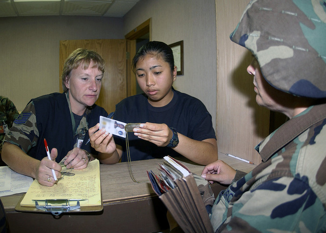 US Air Force (USAF) Technical Sergeant (TSGT) Janette Jackmovich and AIRMAN First Class (A1C) Michelle Aquino, both from the 28th Mission Support Squadron (MSS), 28th Bomb Wing (BW), check dog tags and military identification of personnel waiting in the personnel deployment function line, during Phase I of the base wide pre-deployment for the Air Combat Commands (ACC), up-coming Operational Readiness Inspection (ORI)