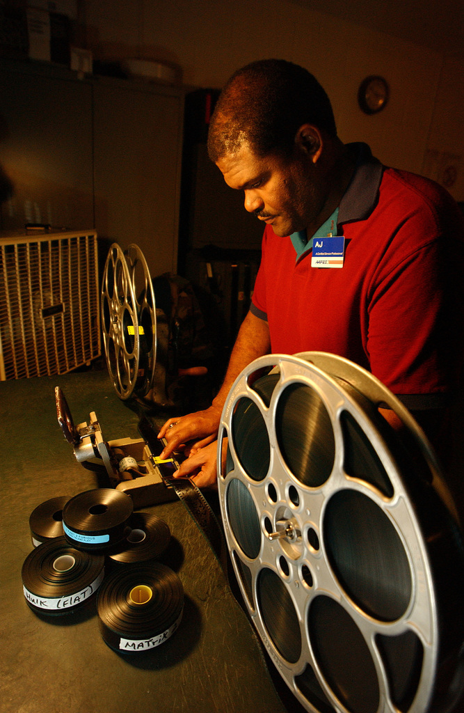 """US Air Force (USAF) Technical Sergeant (TSGT) Elvin Araujo-Guzman, 100th Communications Squadron (CS), works as a Projectionist at the """"Reel Time"""" movie theater, operated by the Army and Air Force Exchange Service (AAFES) at Royal Air Force (RAF) Mildenhall, United Kingdom (UK)"""