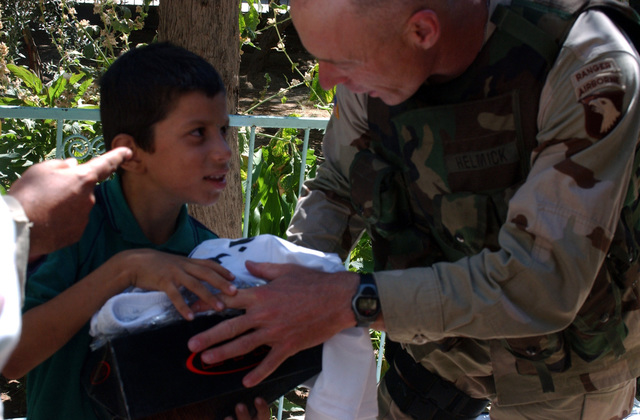 US Army (USA) Brigadier General (BGEN) Frank G. Helmick, Assistant Division Commander of Operations, 101st Airborne Division (Air Assault) hands out a soccer uniform to child at the Virgin Lady Orphanage, Al Quosh, Iraq, during Operation IRAQI FREEDOM. USA personnel in the Division purchased the soccer items to give to the children in the orphanage
