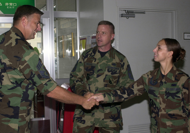 US Air Force (USAF) Command CHIEF MASTER Sergeant (CCMST) Kevin D. Estrem (left), North American Aerospace Defense Command (NORAD), greets SENIOR AIRMAN (SRA) Danielle Hill, 374th Logistics Readiness Squadron (LRS) and Junior Enlisted Council President, during his visit at Yokota Air Base (AB), Japan. CHIEF MASTER Sergeant (CCMSGT) Robert D. Wicks, 374th Airlift Wing (AW), looks on