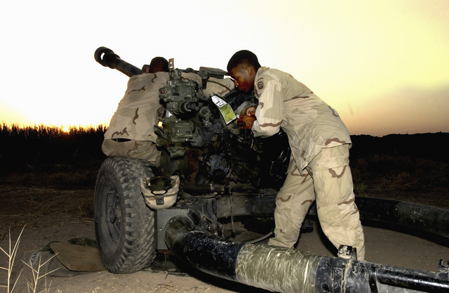 US Army (USA) Sergeant (SGT) Elijah Caddy (right) A/Battery, 2-319 Airborne Field Artillery Regiment, and a member of his unit, records coordinates for a test fire of an M119A1 105mm Lightweight Towed Howitzer, at Baghdad International Airport, Iraq, during Operation IRAQI FREEDOM