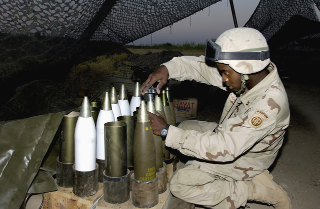 US Army (USA) SPECIALIST (SPC) Kevin Burroughs A/Battery, 2-319th Airborne Field Artillery Regiment, sets the fuse timer for delayed action on M119A1 105mm Lightweight Towed Howitzer rounds just prior to a test firing of the cannon, at Baghdad International Airport, Iraq, during Operation IRAQI FREEDOM