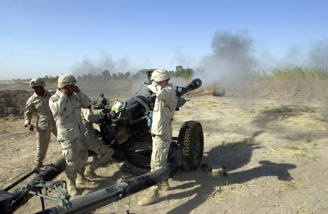US Army (USA) Soldiers assigned to A/Battery, 2-319 Airborne Field Artillery Regiment, fire an M119A1 105mm Lightweight Towed Howitzer during routine training at Baghdad International Airport, Iraq, during Operation IRAQI FREEDOM