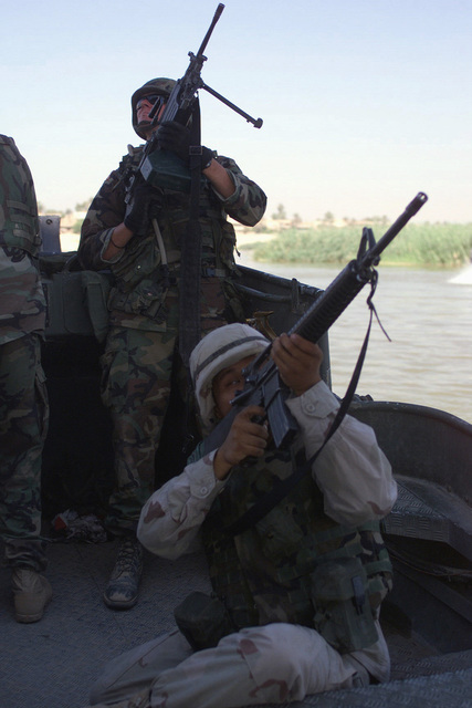 US Army (USA) Soldiers assigned to the 671st Engineer Company, ready their 5.56mm M16A2 rifle and a 5.56mm M249 Squad Automatic Weapon as they pass under a bridge aboard a Mk-2 patrol boat while conducting patrols along the Tigris River in Baghdad, Iraq, during Operation IRAQI FREEDOM