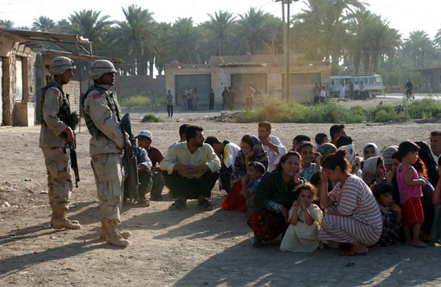 Armed US Army (USA) Soldiers assigned to B/ Company, 588th Engineers, keep an eye on civilians during an early morning raid in a village on the outskirts of Baqubah, Iraq, during Operation IRAQI FREEDOM. The village, along a stretch of road known colloquially as RPG alley, has been the site of many attacks on military convoys and patrols