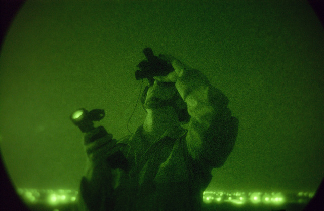 Light enhanced photography showing US Air Force (USAF) Non-Commissioned Officer in Charge (NCOIC) of the Tactical Air Control Party (TACP) for the 4th Air Support Operations Group (ASOG) Detachment 1, using his AN/PVS-7 night vision binocular system, during a close air support exercise at Kirkuk Air Base (AB), Iraq, during Operation IRAQI FREEDOM