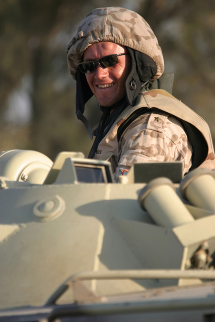 A Ukrainian Army Soldier stands in the commanders hatch aboard a BRT-80A (8x8) armored personnel carrier (APC), in Al Kut, Iraq, during Operation IRAQI FREEDOM