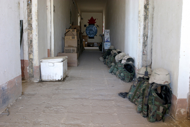 Body armor and helmets belonging to US Marine Corps (USMC) Marines assigned to Kilo/Company, 3rd Battalion, 23rd Marine Regiment (Kilo 3/23) line the hallway inside their living quarters, at As Suwayrah, Iraq, during Operation IRAQI FREEDOM
