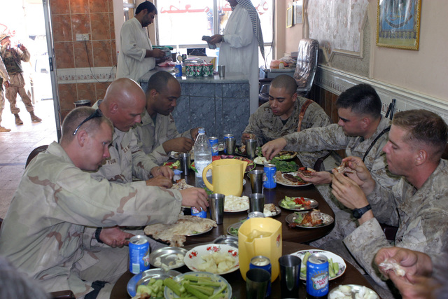 US Marine Corps Reserve (USMCR) Marines assigned to 3rd Battalion, 23 Marine Regiment (3/23), 4th Civil Affairs Group (4th CAG), Marine Forces Reserve (MARFORRES) Combat Visual Information Center (CVIC), and MARFORRES Public Affairs eat lunch at a local restaurant near As Suwayrah, Iraq, during Operation IRAQI FREEDOM