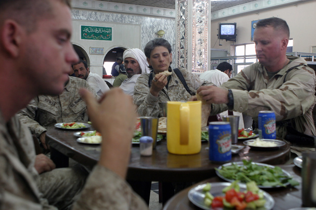 US Marine Corps Reserve (USMCR) Marines eat lunch at a local Iraqi restaurant near As Suwayrah, Iraq, during Operation IRAQI FREEDOM. Pictured left-to-right are: Lance Corporal (LCPL) Ivey, Surveillance and Target Acquisition Platoon, 3rd Battalion, 23rd Marine Regiment (3/23); GUNNERY Sergeant (GYSGT) Heidi Schuerger, SENIOR Non-Commissioned Officer (SNCO), 4th Civil Affairs Group (CAG); and MASTER Sergeant (MSGT) James Roberts, SENIOR Non-Commissioned Officer In Charge (SNCOIC) MARFORRES, Combat Visual Information Center (CVIC)