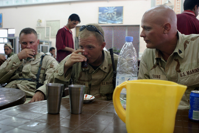 US Marine Corps Reserve (USMCR) Marines enjoy a hot cup of tea after eating lunch at a local restaurant near As Suwayrah, Iraq, during Operation IRAQI FREEDOM. Pictured left-to-right are: MASTER Sergeant (MSGT) James Roberts, SENIOR Non-Commissioned Officer In Charge (SNCOIC), Marine Forces Reserve (MARFORRES), Combat Visual Information Center (CVIC); Corporal (CPL) Paul Garner and Sergeant (SGT) Kevin Young, both assigned to Kilo/Company 3rd Battalion, 23rd Marine Regiment (Kilo 3/23)