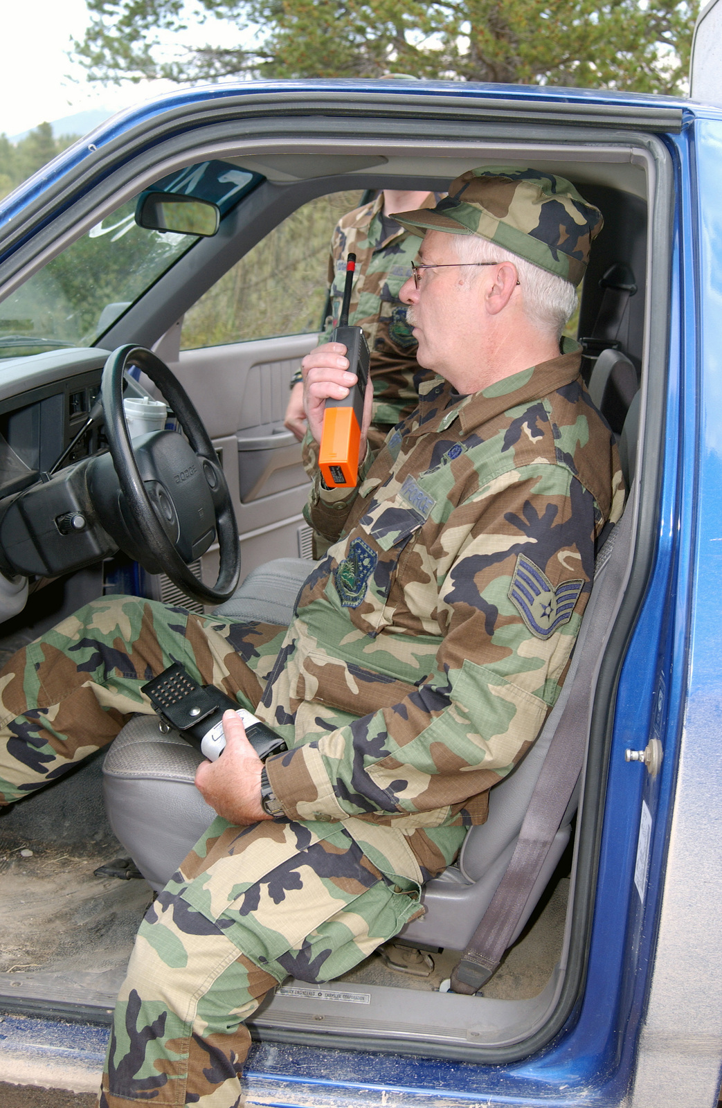 US Air Force (USAF) STAFF Sergeant (SSGT) Charles Heit, 120th Fighter Wing (FW) Montana Air National Guard (MTANG) checks in by radio with security control while assigned to provide security for the property owners living close to wild fires burning near Alice Creek, located in Lincoln, Montana