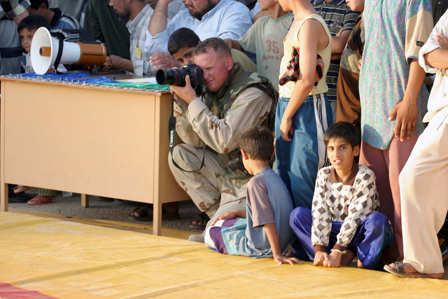 US Marine Corps (USMC) MASTER Sergeant (MSGT) James Roberts, SENIOR Non-Commissioned Officer In Charge (SNCOIC), Marine Forces Reserve (MARFORRES) Combat Information Center (CVIC), uses a still digital camera to document activities from the sideline, during a wrestling match held for Iraqi youths at Al Kut, Iraq, during Operation IRAQI FREEDOM