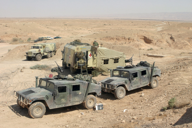 Two US Marine Corps (USMC) High-Mobility Multipurpose Wheeled Vehicles (foreground), equipped with 7.62mm M2HB machine guns, sit with a Ukraine Army GAZ-66 (4X4) 2,000kg Ambulance Van and Ural4320-10 (6x6) 4,500kg truck, at the Iran/Iraq border crossing located at Badrah, Iraq, during Operation IRAQI FREEDOM