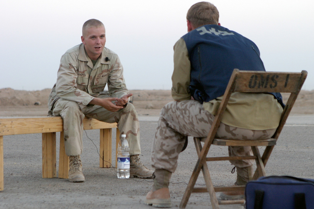 US Marine Corps Reserve (USMCR) Lance Corporal (LCPL) Knopov (background), assigned to the 4th Civil Affairs Group (CAG), is interviewed by a member of the Ukraine Army television new crew at Blair Field in Al Kut, Iraq, during Operation IRAQI FREEDOM. LCPL Knopov, a former Russian citizen, immigrated to the United States from Moscow, after his mother married a US Air Force (USAF) Officer