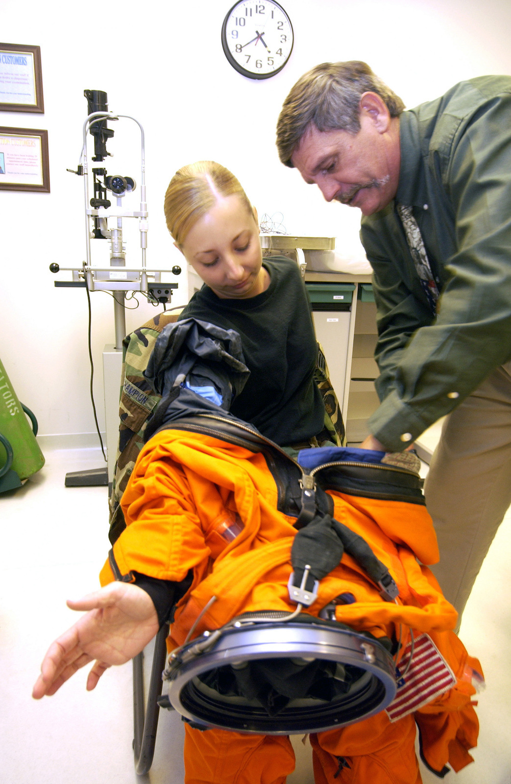 US Air Force (USAF) SENIOR AIRMAN (SRA) Jennifer Champion, 65th Medical Group, gets assistance from a National Aeronautics and Space Administration (NASA) Instructor, as she suits up in an authentic NASA spacesuit, at Lajes Field, Azores, Portugal. SRA Champion is one of several medical personnel receiving specialized training from members of the Department of Defense (DOD), Space Flight Support Office. Training is vital to Lajes medical personnel, due to the fact that it is one of the alternate emergency landing sites for the Space Shuttle