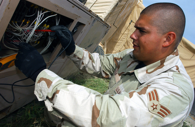 US Air Force (USAF) SENIOR AIRMAN (SRA) Reginald Avila, 321st Expeditionary Civil Engineering Squadron (ECES), troubleshoots a control circuit on an Environmental Control Unit, while deployed at Masirah Air Base (AB), Oman, during Operation IRAQI FREEDOM