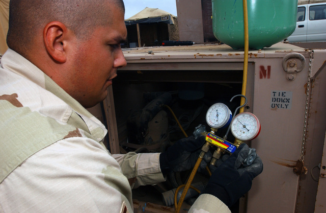 US Air Force (USAF) SENIOR AIRMAN (SRA) Reginald Avila, 321st Expeditionary Civil Engineering Squadron (ECES), checks the refrigerant charge on an Environmental Control Unit, while deployed at Masirah Air Base (AB), Oman, during Operation IRAQI FREEDOM