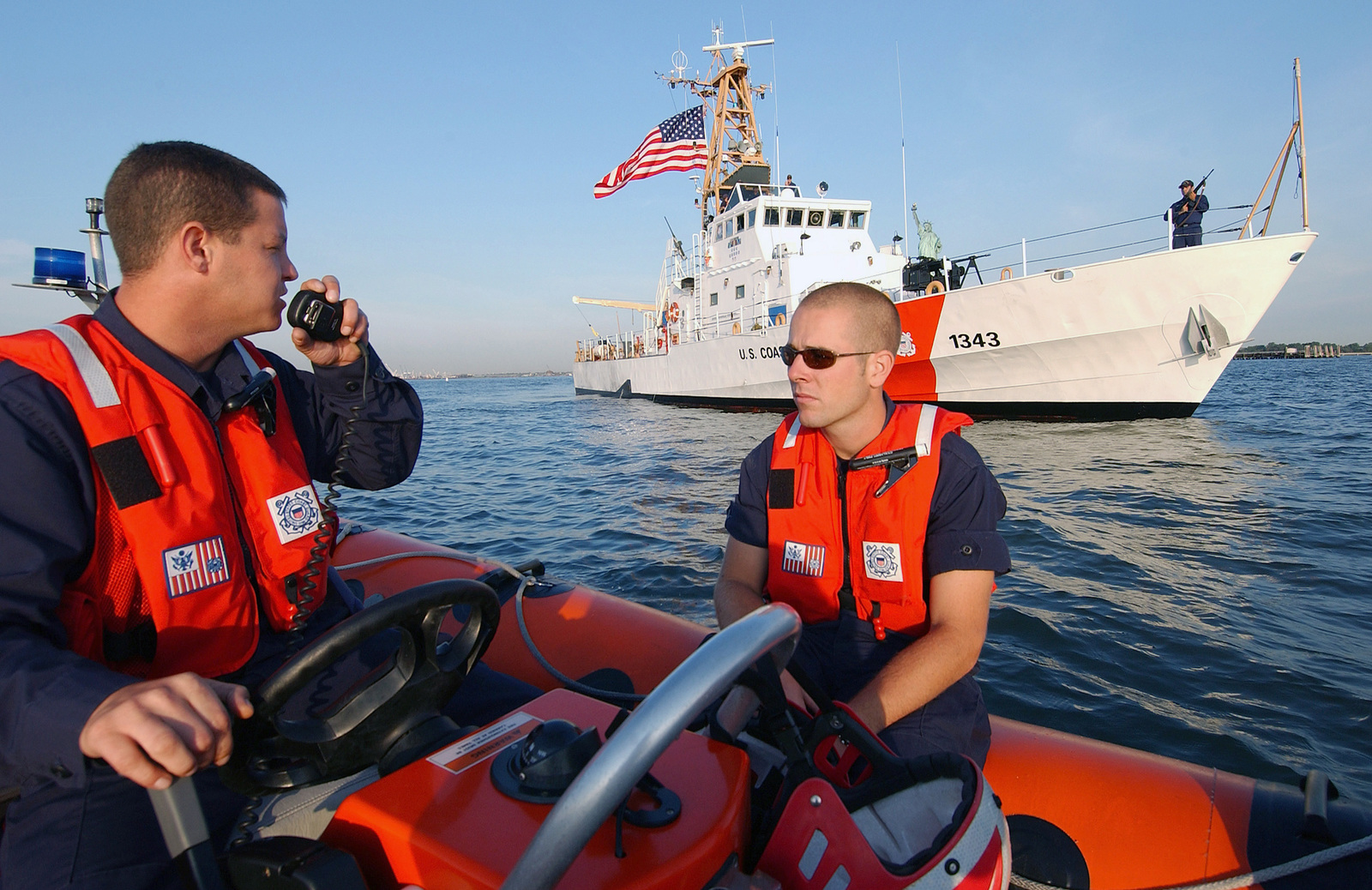 US Coast Guard (USCG) Boatswain's Mate First Class (BM1) William Lappin (left) and SEAMAN (SN) Ken Rose, make radio contact with the USCG Island Class; Patrol Craft, BAINBRIDGE ISLAND (WPB) 1343), while patrolling the New York Harbor aboard a Rigid Hull Inflatable Boat (RHIB), during a homeland security mission