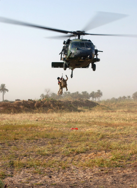 Two US Air Force (USAF) Pararescuemen from the 101st Expeditionary Rescue Squadron (ERS), practice a tandem live hoist onto an HH-60G Pave Hawk helicopter during a Combat Search And Rescue (CSAR) exercise. The exercise sharpens the skills of CSAR teams deployed to Baghdad International Airport (BIA), Iraq, during Operation IRAQI FREEDOM