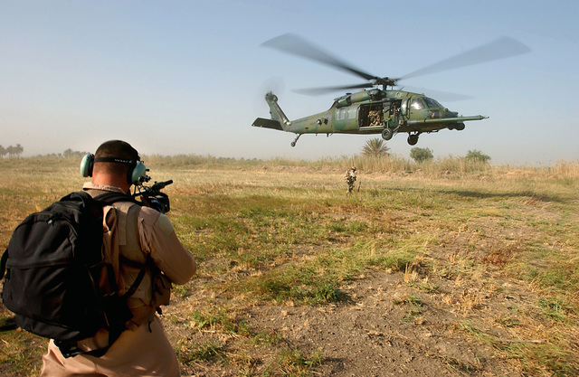 US Air Force (USAF) MASTER Sergeant (MSGT) Abdon Padilla, a Combat Camera videographer deployed to Baghdad International Airport (BIA), Iraq (IRQ), from Lackland Air Force Base (AFB), Texas (TX), documents an HH-60G Pave Hawk helicopter during a Combat Search and Rescue (CSAR) exercise, during Operation IRAQI FREEDOM