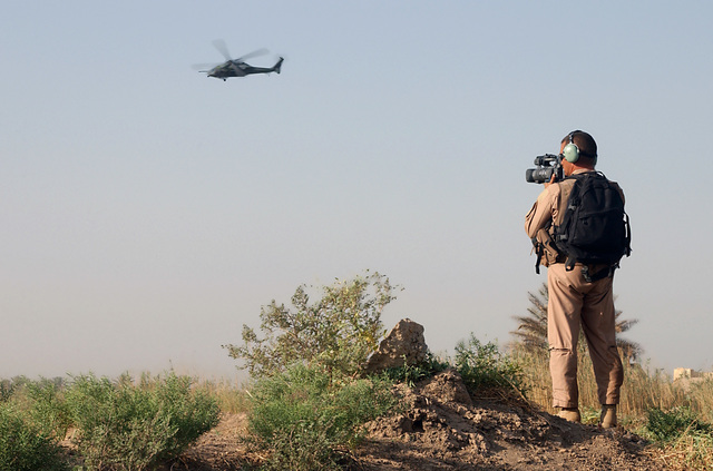 US Air Force (USAF) MASTER Sergeant (MSGT) Abdon Padilla, a Combat Camera videographer deployed to Baghdad International Airport (BIA), Iraq (IRQ), from Lackland Air Force Base (AFB), Texas (TX), documents a Combat Search and Rescue (CSAR) exercise, during Operation IRAQI FREEDOM