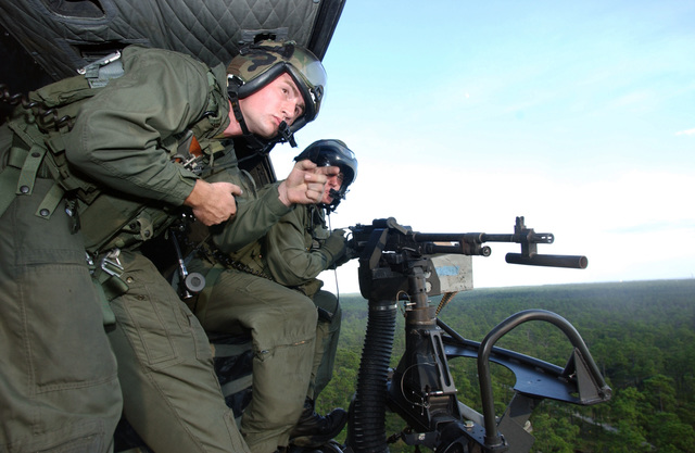 "US Marine Corps (USMC) Lance Corporal (LCPL) Jason Kingsland, from Marine Helicopter Light Attack Squadron 773 (HMLA-773), onboard an UH-1N Iroquois Twin Huey helicopter takes aim with a door mounted M-60 7.62mm Machine Gun, while Sergeant (SGT) Brian ""Soup"" Cambell, left, calls out directions during a live-fire training mission over Eglin Air Force Base (AFB), Florida"