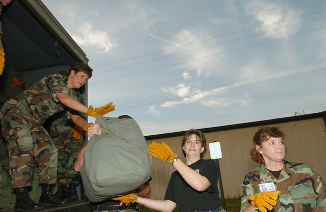 US Air Force (USAF) MASTER Sergeant (MSGT) Valerie Murphy (center), Non-Commissioned Officer In Charge (NCOIC) of Employment/Relocation at the Virginia Air National Guard's (VAANG) 192nd Fighter Wing (FW), load deploying members baggage onto a truck. The 192d FW is participating in a 90 day Aerospace Expeditionary Forces (AEF) tour to Southwest Asia in support of Operation IRAQI FREEDOM