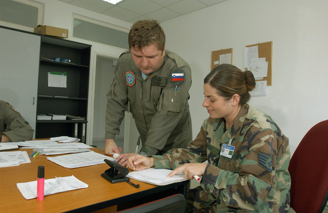 Captain (CAPT) Rek Branko, left, a Bel-412 helicopter pilot with the Slovenia Air Force (SAF), reviews his post flight documentation with the Non-Commissioned Officer in Charge (NCOIC) of Helicopter Operations at Graff Ignateivo Air Base (AB), Bulgaria (BG), US Air Force (USAF) STAFF Sergeant (SSGT) Kristine Oliver, from Headquarters Air South during Cooperative Key 2003