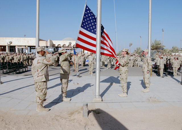 At Baghdad International Airport (BIA), Iraq, US Air Force (USAF) SENIOR MASTER Sergeant (SMSGT) John Calfa, salutes the flag while personnel assigned to the 447th Air Expeditionary Group (AEG), Honor Guard retire the colors during a Remembrance Ceremony honoring the victims of the terrorist attacks of September 11th, 2001