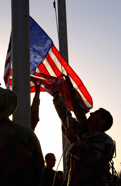 At the Baghdad International Airport (BIA), Baghdad, Iraq, US Air Force (USAF) personnel from the 447th Air Expeditionary Group (AEG) Command STAFF raise an American flag during a memorial service dedicated to those who lost their lives September 11th, 2001