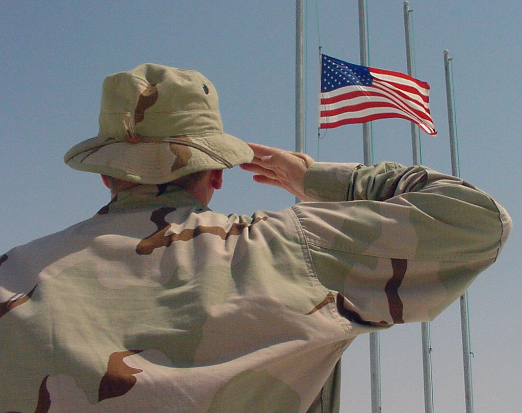 Deployed US Air Force (USAF) member salutes the American flag, posted at half-mast in observance of Patriot Day September 11. The base flag flew at half-mast the entire day in remembrance of the victims of September 11, 2001, in New York, the Pentagon and Pennsylvania