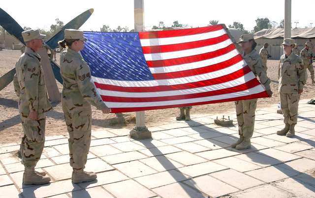 Retiring the colors at Baghdad International Airport (BIA), Iraq, is the US Air Force (USAF) Honor Guard, left to right, SENIOR AIRMAN (SRA) Ken Whelchel, STAFF Sergeant (SSGT) Beth Roe, SSGT Sally Davis and SSGT Tracy Willen, from the 447th Air Expeditionary Group (AEG), during a Remembrance Ceremony honoring the victims of the terrorist attacks of September 11th, 2001