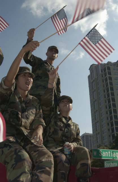 """US Air Force (USAF) members of MacDill Air Force Bases (AFB) """"NOC 3"""" (No One Comes Close Council), a leadership organization comprised of E-4's and below from all services currently stationed at MacDill) join the Florida National Guard Junior Enlisted Council, the Salvation Army, The Bayshore Patriots Organization, and other patriotic citizens on Bayshore Boulevard in Tampa Florida (FA). The gathering of a diverse group of people, all waving flags, seen as a show of community and the American spirit in remembrance of those who died in the September 11th attacks exactly two years ago"""