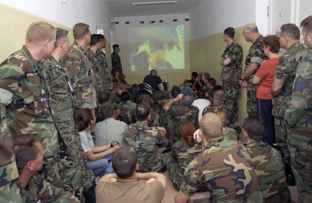 US Air Force (USAF) personnel watch a memorial slide show as part of a commemoration ceremony honoring those who lost their lives in the attacks of September 11th, 2001, during exercise RESCUER/MEDCEUR 03