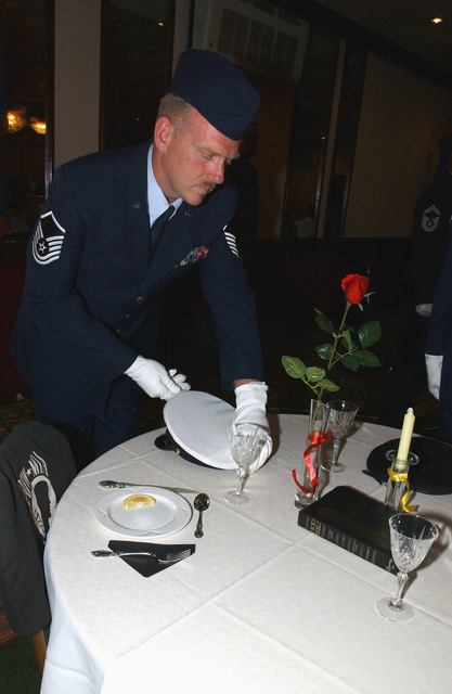US Air Force (USAF) MASTER Sergeant (MSGT) Author House, Non-Commissioned Officer in Charge (NCOIC) of Medical Repairs, 48th Medical Support Squadron (MDSS), Royal Air Force (RAF) Lakenheath, United Kingdom (UK), participates in a table setting ceremony at the Eagles Landing officers club. The ceremony dedicated to prisoners of war and those missing in action from all branches of the military