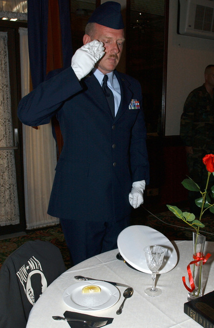 US Air Force (USAF) MASTER Sergeant (MSGT) Author House, Non-Commissioned Officer in Charge (NCOIC) of Medical Repairs, 48th Medical Support Squadron (MDSS), Royal Air Force (RAF) Lakenheath, United Kingdom (UK), renders a salute at a table setting ceremony at the Eagles Landing officers club. The ceremony dedicated to prisoners of war and those missing in action from all branches of the military