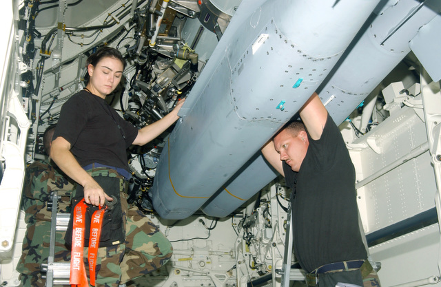 US Air Force (USAF) STAFF Sergeant (SSGT) Kari Miller (left) and SSGT Mitchell Swindell, Weapons Loading Technicians, 509th Aircraft Maintenance Squadron (AMXS), Whiteman Air Force Base (AFB), Missouri (MO), install safety pins to secure the Joint Stand-Off Weapons (JSOW) in the B-2 Spirit bomber during Exercise CORONET DRAGON 49