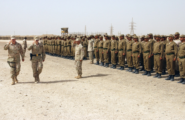US Army (USA) Sergeant Major (SGM) Richard Fischer, Non-Commissioned Officer In Charge (NCOIC), Iraqi Civil Defense Course (ICDC), and USA Brigadier General (BGEN) Curtis M. Scaparrotti, Assistant Division Commander (Maneuver), 1ST Armored Division (AD), review the new Iraqi Civil Defense Force troops at their graduation ceremony. The ICDC conducted weekly in Baghdad, Iraq, to train new Iraqi recruits on soldier skills and to prepare them to work with coalition forces supporting Operation IRAQI FREEDOM