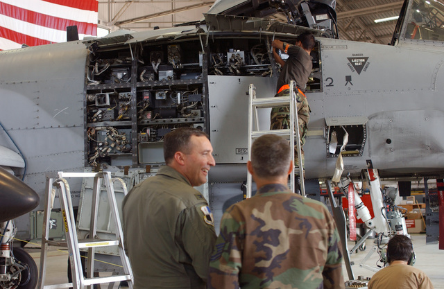 US Air Force (USAF) MASTER Sergeant (MSGT) Kevin Davidson, 52d Equipment Maintenance Squadron (52d EMS), shows USAF Colonel (COL) Stephen P. Mueller, Commander, 52nd Fighter Wing (FW), Spangdahlem Air Base (AB), Germany, the process as Airmen of the 52nd EMS perform extensive inspections on USAF A-10 Thunderbolt II aircraft. USAF Thunderbolt II aircraft undergo this kind of inspection after every 400 and 800 hours of flight. In this very rare case, the 52nd EMS triple docked three aircraft at once: one in the first day of inspection, one in the seventh day, and one on the twelfth and final day on Spangdahlem AB