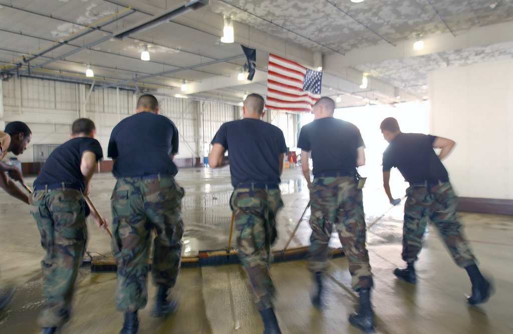 US Air Force (USAF) AIRMAN First Class (A1C) Philip Durrschmidt (left), USAF AIRMAN (AMN) Bruce Parker, USAF SENIOR AIRMAN (SRA) Thomas Pavelchak, AMN Chase Washburn and A1C Marcos Flores, 1ST Equipment Maintenance Squadron (EMS) clear the remnants of flood waters from an aircraft maintenance hanger at Langley Air Force Base (AFB), Virginia (VA). Over two feet of flooding occurred in most of the hangars on the coastal side of Langley AFB during Hurricane Isabel