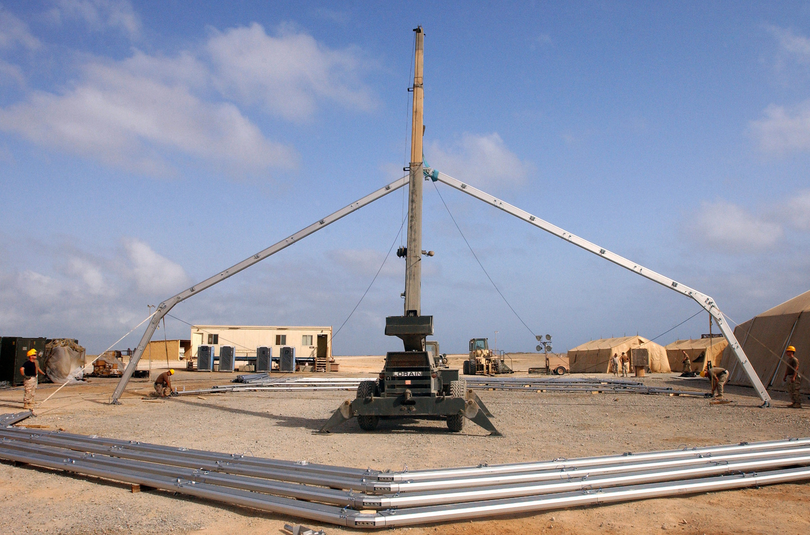 US Air Force (USAF) personnel from the 49th Materiel Maintenance Group (MMG) Basic Expeditionary Airfield Resources (BEAR) Base Team, Holloman Air Force Base (AFB), New Mexico (NM), and the 321st Expeditionary Civil Engineer Squadron  (ECES) Structures Team use a light Lorain hydraulic crane to erect a Large Area Maintenance Shelter (LAMS). The shelter will store and protect aircraft equipment from the elements during Operation IRAQI FREEDOM