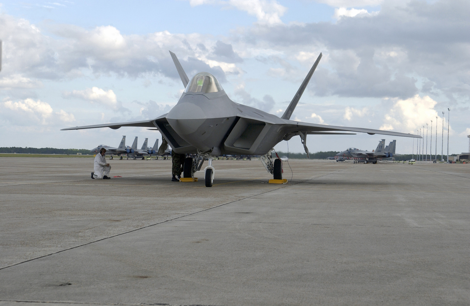 The US Air Force (USAF) F/A-22 Raptor (number 18) sits on the tarmac just after landing. Visible under the wings are the F-15C Eagle fighter jets of the 95th Fighter Squadron (FS). This is the first F/A-22 Raptor delivered to the Air Force. It will become part of the 43rd Fighter Squadron (FS) which will be responsible for training pilots to fly the new air superiority fighter