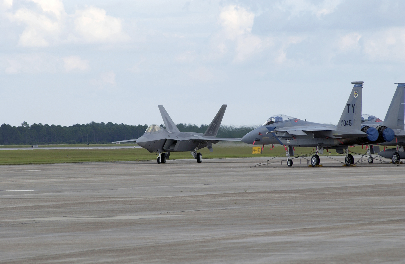 """The US Air Force (USAF) F/A-22 Raptor (number 18) taxis by USAF F-15C Eagle fighter jets of the 95th Fighter Squadron (FS) after landing. This is the first F/A-22 Raptor delivered to the Air Force. It will become part of the 43rd Fighter Squadron (FS) which will be responsible for training pilots to fly the new air superiority fighter. The plane is piloted by USAF Lieutenant Colonel (LTC) Jeffrey """"Cobra"""" Harrigian, Commander, 43rd Fighter Squadron (FS), 325th Fighter Wing (FW), Air Education and Training Command (AETC), Tyndall Air Force Base (AFB), Florida (FL)"""