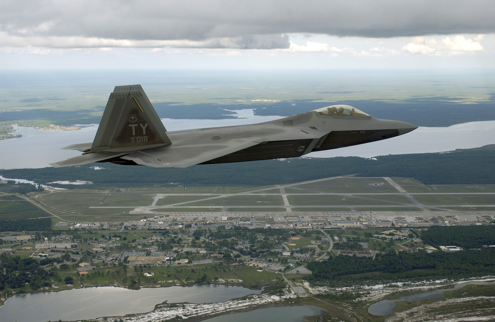 """US Air Force (USAF) Lieutenant Colonel (LTC) Jeffrey """"Cobra"""" Harrigian, Commander, 43rd Fighter Squadron (FS), 325th Fighter Wing (FW), Air Education and Training Command (AETC), Tyndall Air Force Base (AFB), Florida (FL), flies Raptor 01-018, over its new home. This is the first of 48 new USAF F/A-22 Raptors assigned to Tyndall's 325th FW. The flight, took place September 26, 2003, is a major milestone and will now enable the 43rd FS to begin formally training pilots to fly this next-eration fighter. The F/A-22 combines stealth, supercruise, maneuverability and many other features enabling a first look, first shot, first kill capability that will provide continued air dominance for..."""